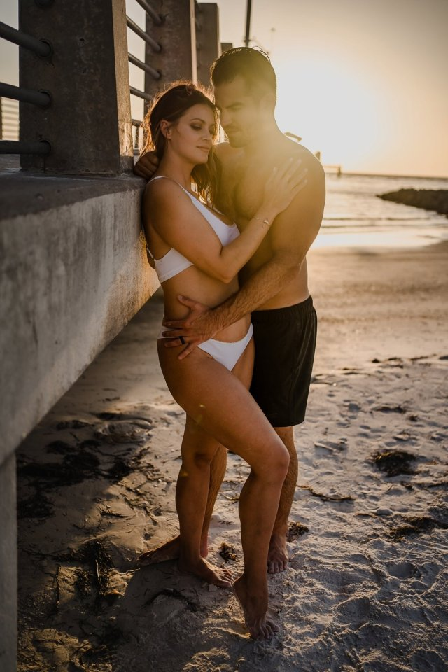 A couple posing on the beach for a spicy ocean photoshoot with Tampa engagement photographer Tami Keehn