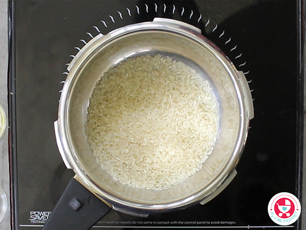 Add rice in pressure cooker.
