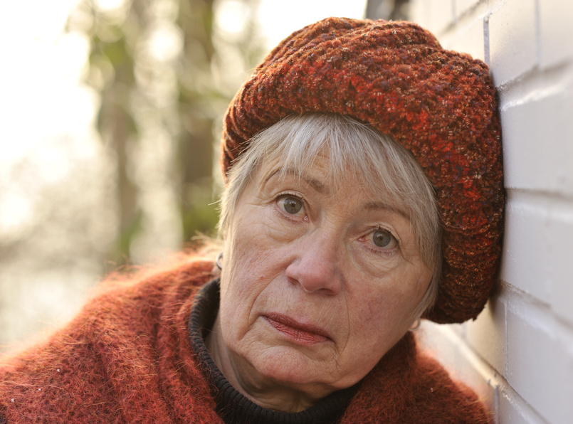 Older woman leaning against a wall with a look of despair on her face.