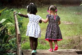 Two little girls walking across a bridge.