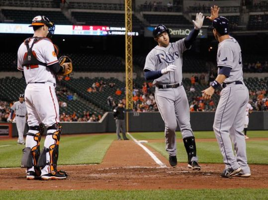 Evan Longoria, center, high-fives Ben Zobrist in front of Matt Wieters after getting the Rays within 5-4 with a two-run homer in the eighth. (Photo courtesy of Getty Images)