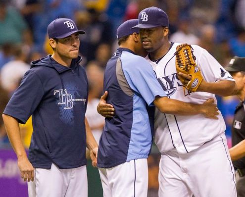 Roberto Hernandez, right, gets a hug from rookie Chris Archer after pitching his first complete game since September 2010. (James BOorchuck/Tampa Bay Times)