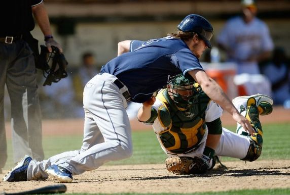 Wil Myers dives back to touch home plate and gets tagged out by Stephen Vogt in the seventh inning on September 1, 2013. (Photo by Thearon W. Henderson/Getty Images)