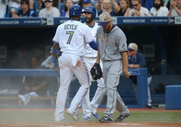 Jose Reyes is congratulated by Jose Bautista after scoring a run in the first inning as Erik Bedard looks on. (Photo courtesy of Tom Szczerbowski/Getty Images)