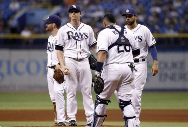 Jose Molina walks in to speak with pitcher Jeremy Hellickson as manager Joe Maddon makes his way to take Hellickson off the mound after he allowed four runs during the fifth inning. (Photo courtesy of Brian Blanco/Getty Images)