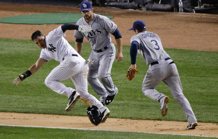 Jacoby Ellsbury is caught in a rundown as third baseman Evan Longoria chases him down between third and home as pitcher Xavier Cedeno looks on. (Photo credit: AP Photo/Julie Jacobson)