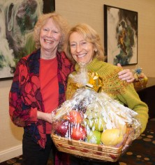 Following the morning discussions, attendees gathered for a prize raffle, with Anne Strozier (left) presenting Joyce Carpenter with one of the two large fruit baskets donated by Publix Supermarkets.