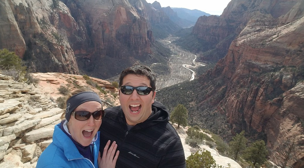 April and Tiago at the top of angels landing with looks of shock on their faces