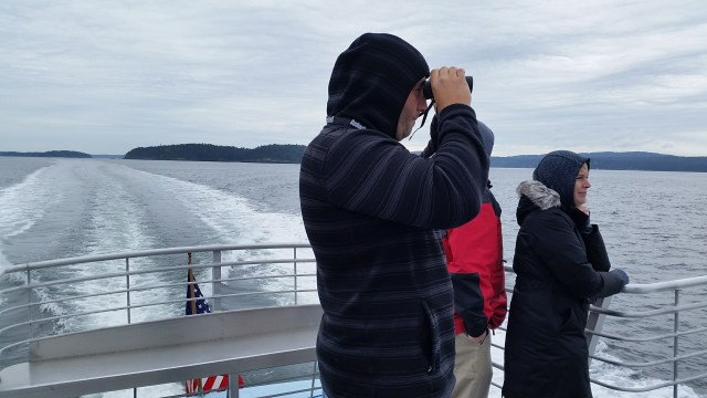 My husband using binoculars on the back of the whale watch boat looking for whales