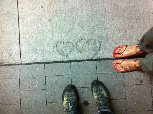 pair of feet in walking boots, pair of feet in sandals, standing on bricks and facing 2 hearts found in concrete