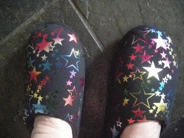 feet with slippers on dark grey slate floor. The slippers have a shiny star pattern in rainbow colours