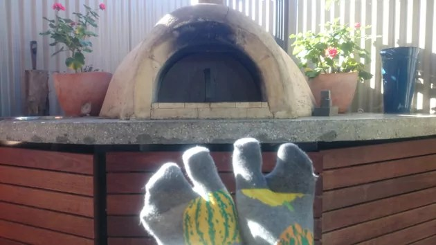 feet in tabi socks, in front of an outdoor pizza oven