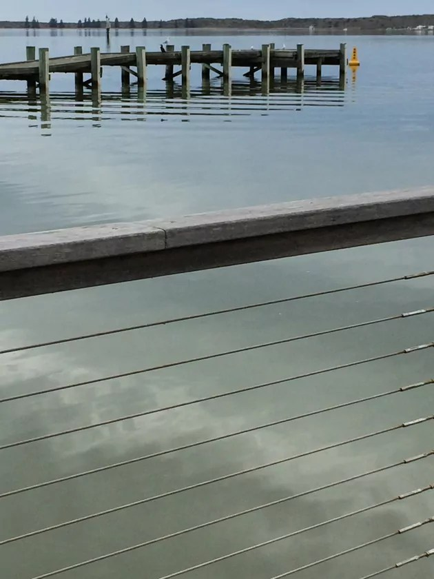 view from wharf to jetty, across rippled pale blue water