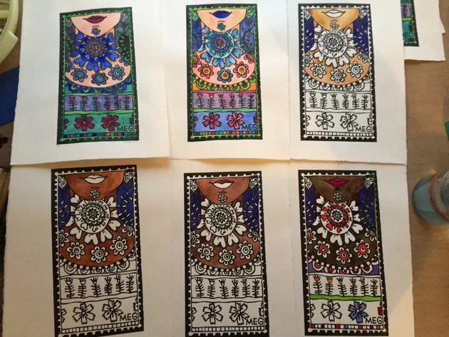 6 Lino prints of a woman's neck with colourful patterns, are laid out beside each other on the artist's table