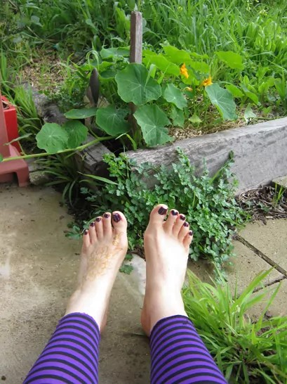 bare feet beside a garden bed with nasturtiums growing in it