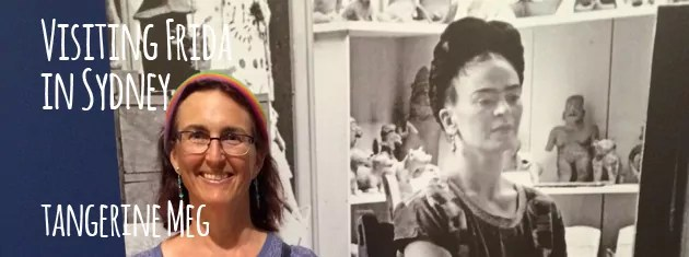 """Header image for """"Visiting Frida in Sydney"""" blog post featuring Tangerine Meg posing in front of a big photographic mural of Frida Kahlo in her studio."""