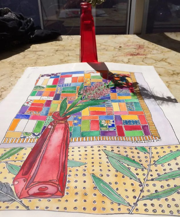 Sun shining in a window on almost complete bottle brush painting. Painting has yellow spotty cloth and quilt as background. The table surface is goldy swirly laminate table. The red bottle featured in the painting is seen on the table too.