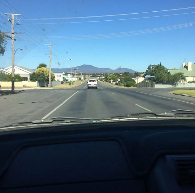 view out a windscreen at a road and a blue sky