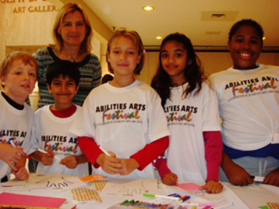 A photo of five kids wearing Abilities Art Festival T shirts. They all look at the camera. An adult woman stands behind them