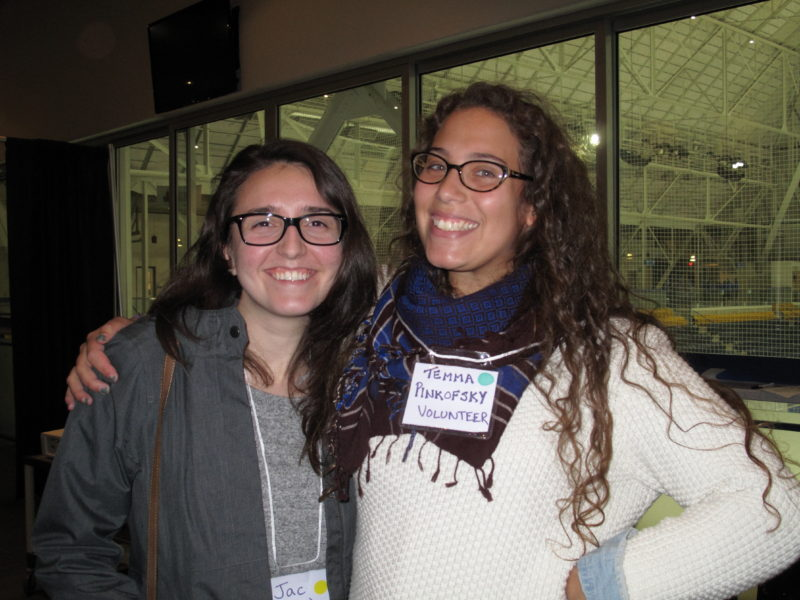 "This image is a waist-up photo of two people standing next to each other, smiling and posing for the picture. The person on the left side of the photo is wearing a light grey shirt, a dark grey jacket, and black-framed glasses. They have long, straight, dark brown hair. The person next to them is wearing a white sweater, a blue scarf around their neck and black-framed glasses. They are wearing a name tag that says ""Temma Pinkofsky Volunteer"". They have long, wavy, light brown hair. The person in white has their right arm around the person in grey and their left is placed on their waist. The person in grey has their right arm in their pocket. Both people are caucasian. The two are standing in a room and behind them there is a window through which an indoor ice rink can be seen."