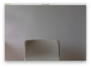 A screen shot of a photograph of the top of a beige chair in front of a beige wall