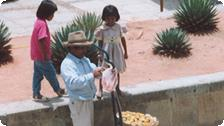 A man selling apricots to little girls.