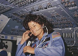 Astronaut Sally Ride in NASA uniform in front of bank of switches in the Space Shuttle