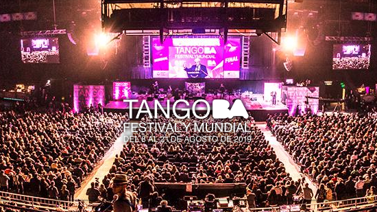 The photo shows a stage in the background distance, and portions of a large auditorium filled to capacity with people watching a world competition of Argentine tango.
