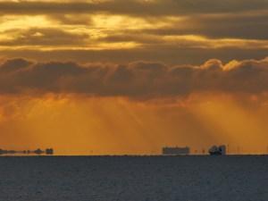 夜明けの水平線を行く漁船