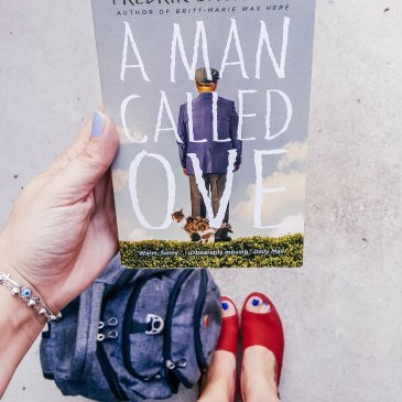 holding book and looking down at bag and shoes