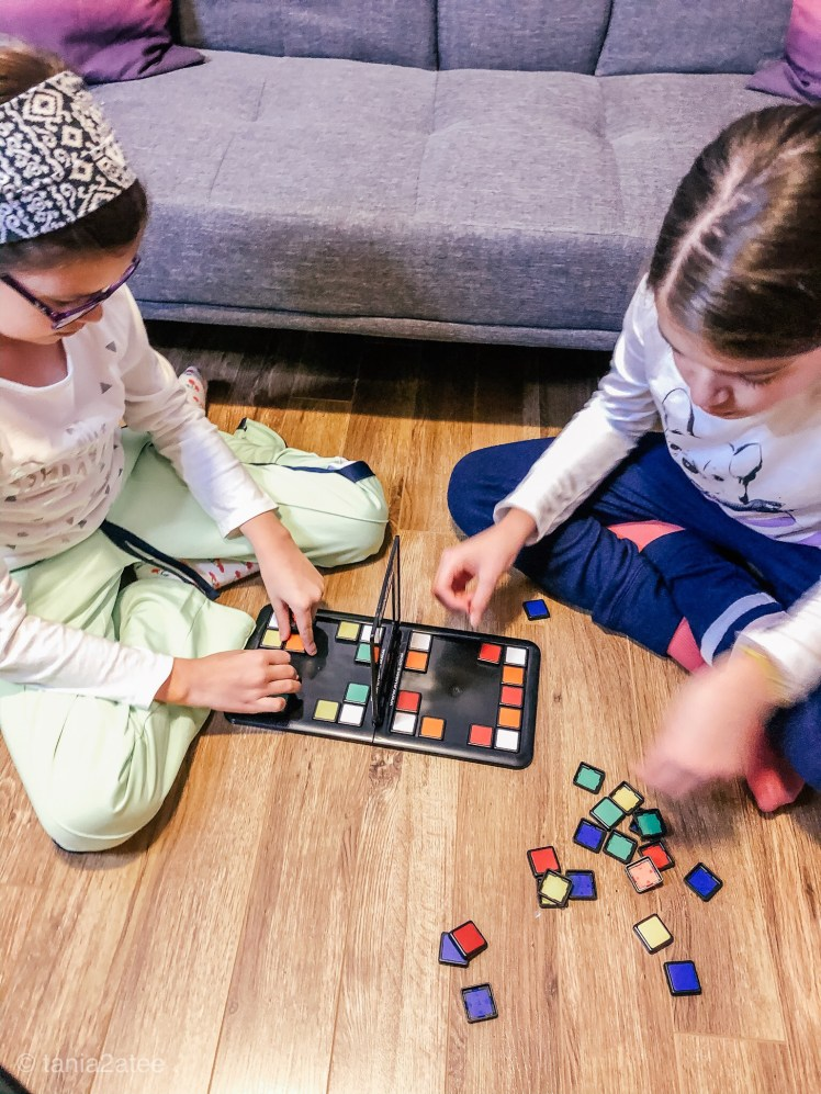 two girls assembling Rubik's Race game