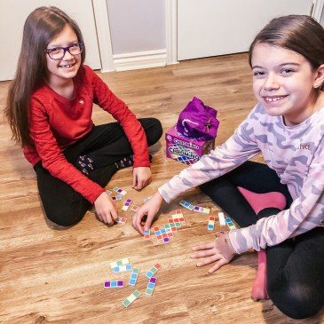 two girls playing domino game with coloured pieces