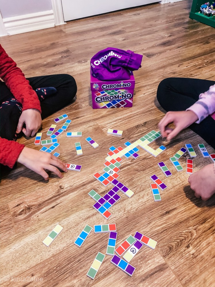 close up of girls playing colourful dominos game