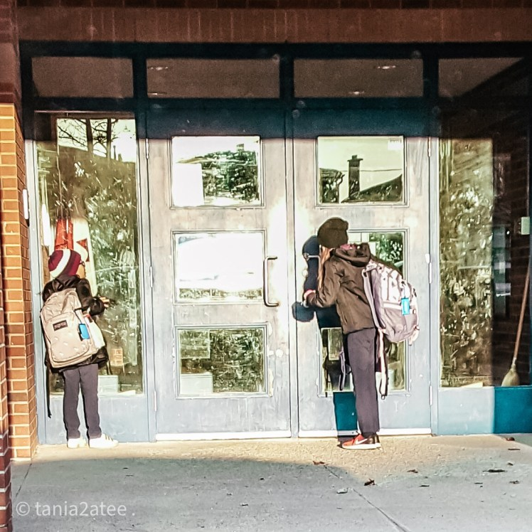 two girls looking into school doors from the outside