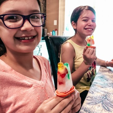 two girls holding homemade ice pops with gummy bears