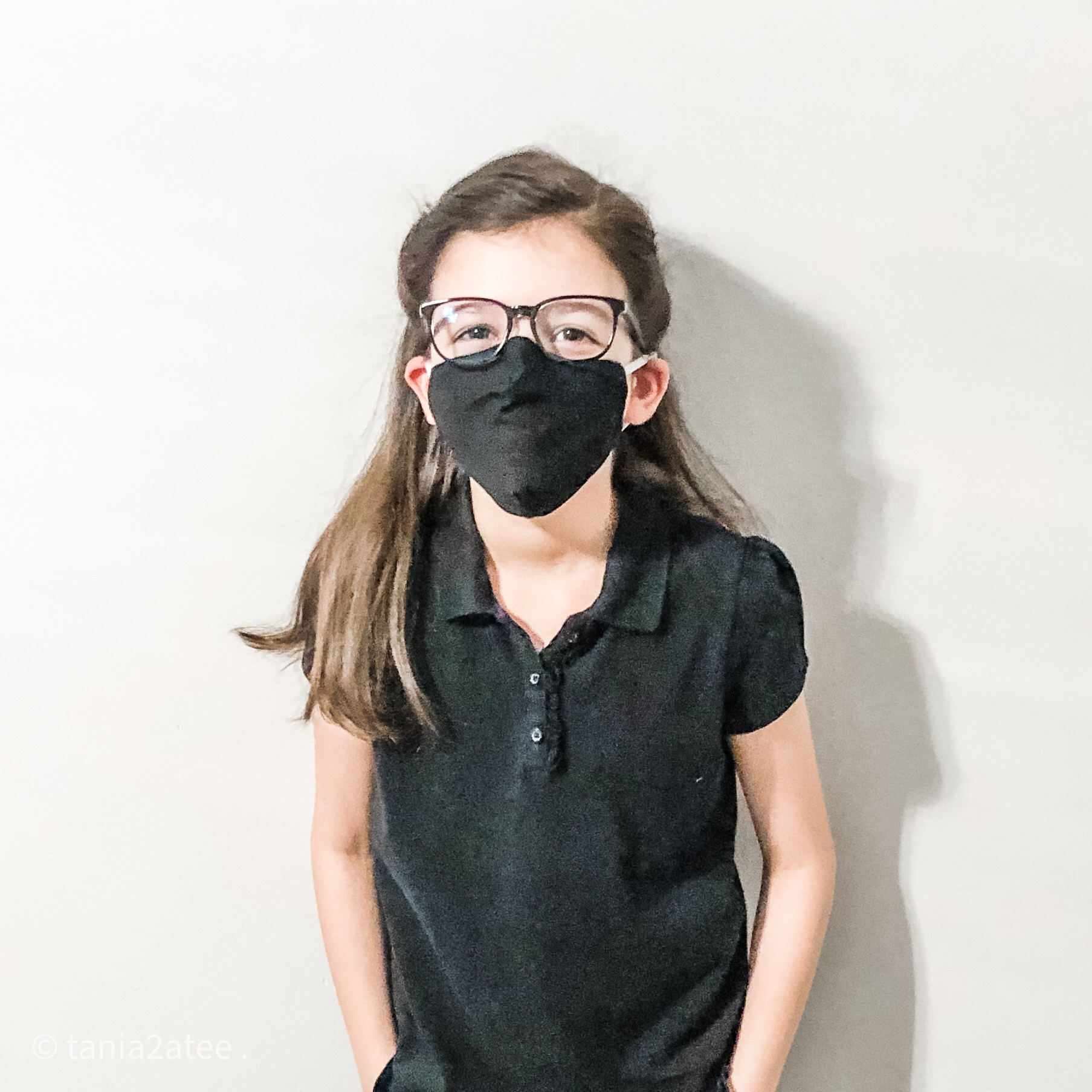 girl posing for camera with hands in her pockets wearing black top and pants, glasses and black face mask