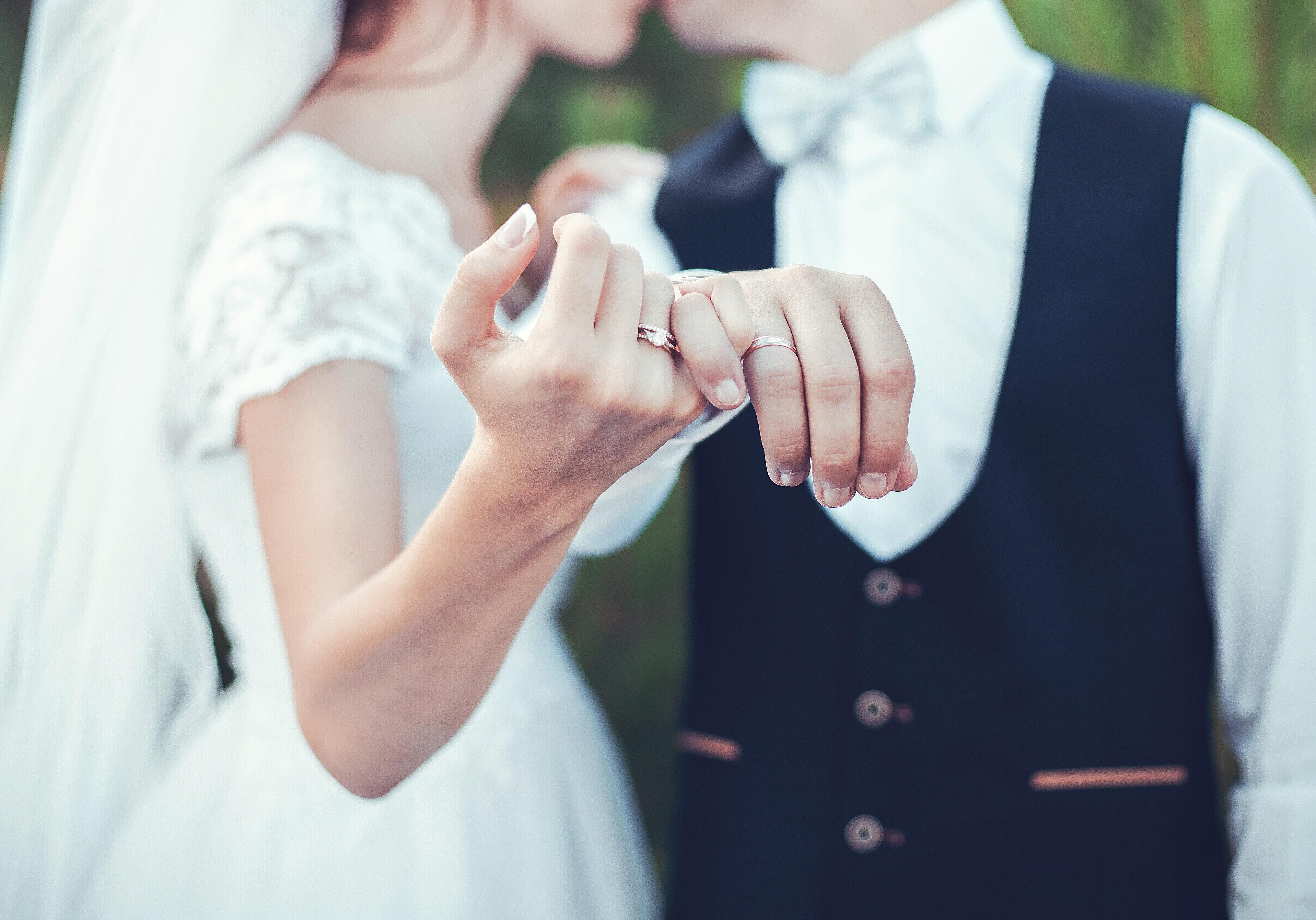 newlyweds intertwining pinkies