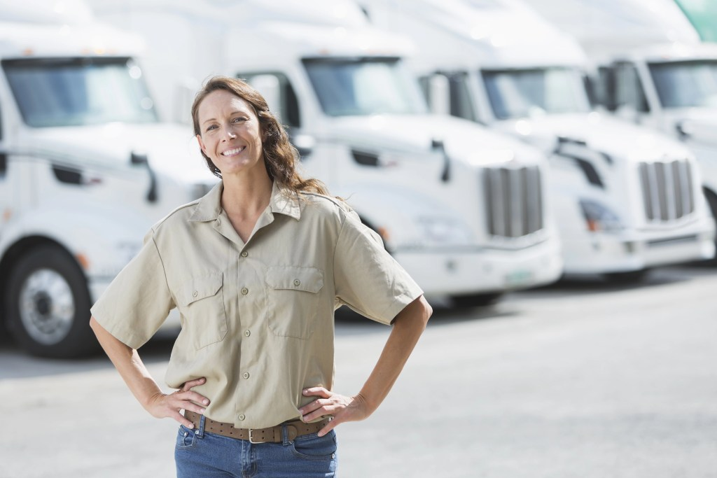 Woman standing in front of semi-trucks