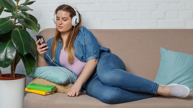 ソファに横になって音楽を聞く女性