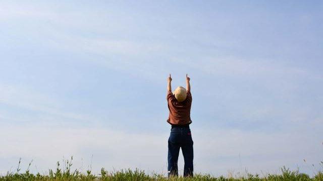 空に手を上げる人