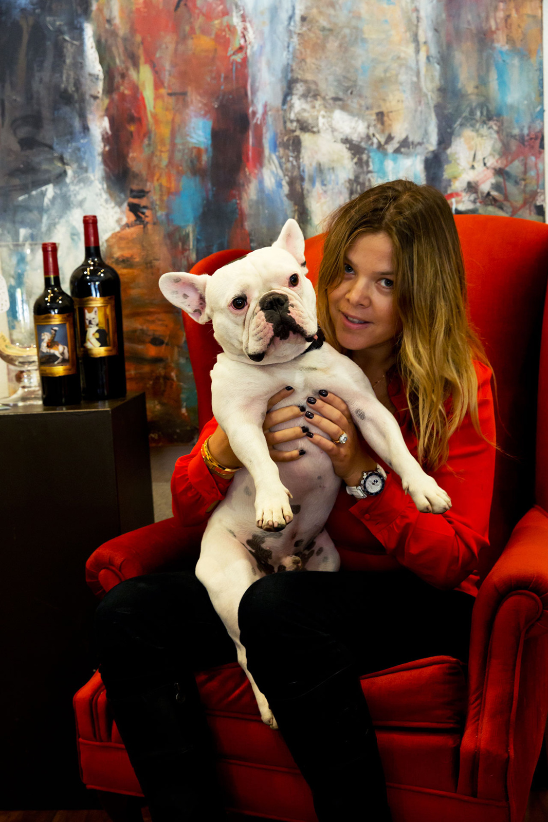 Woman holding up Frenchie dog with 2 wine bottles close by