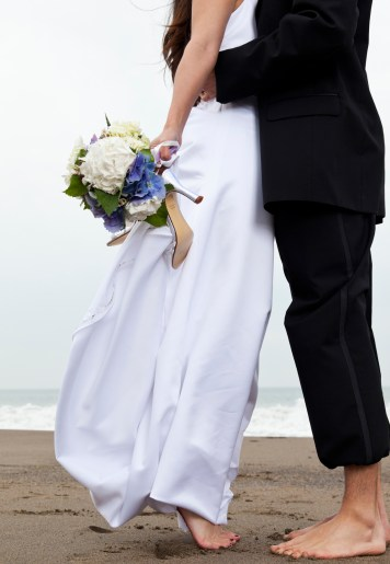 Barefoot bride and groom at beach