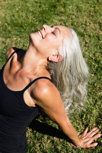 Smiling woman with long grey hair on grass