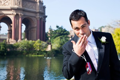 Groom blowing a kiss to the camera at Palace of Fine Arts