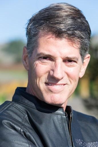 Headshot taken outdoors of man with grey hair