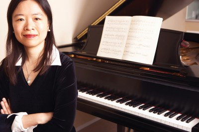 Asian woman with crossed arms in front of piano
