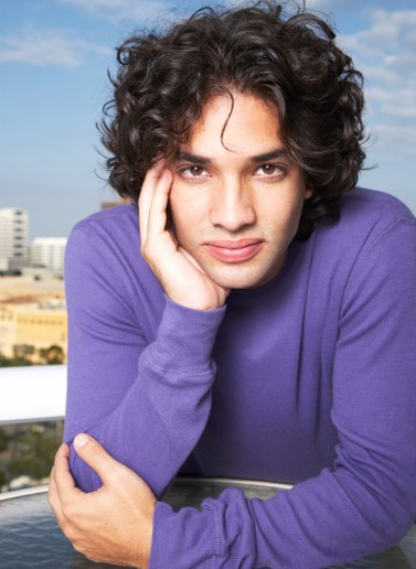 Headshot of man with curly hair outdoors