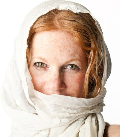 Headshot of red headed girl with white scarf over her head