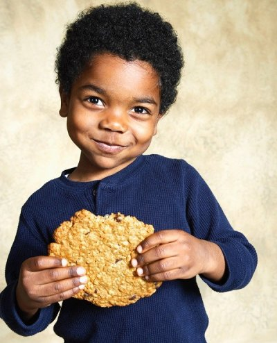 Little African-American boy with big cookie
