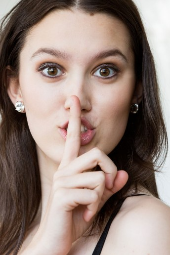 "Headshot of girl with finger on lips saying, ""Shhhh!"""